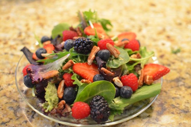 greens with berries and pecans