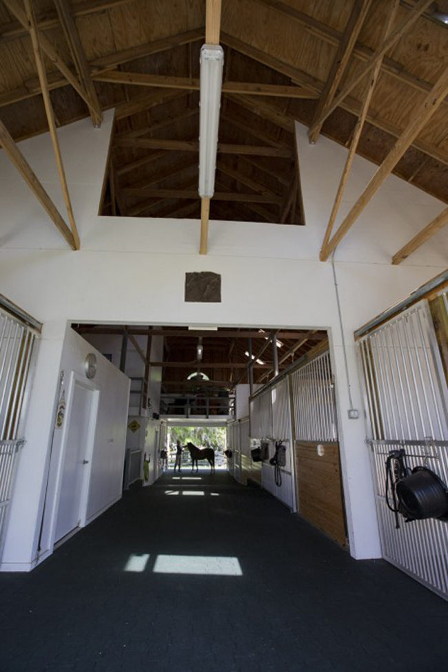 The interior of the barn aisle with high ceilings and fans