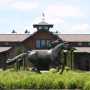 Large running horse statue in front of the barn