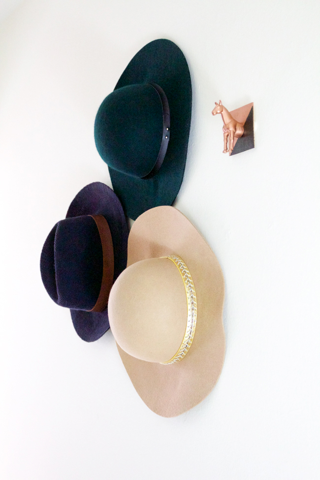 Hats hanging on DIY horse head hooks in the hallway