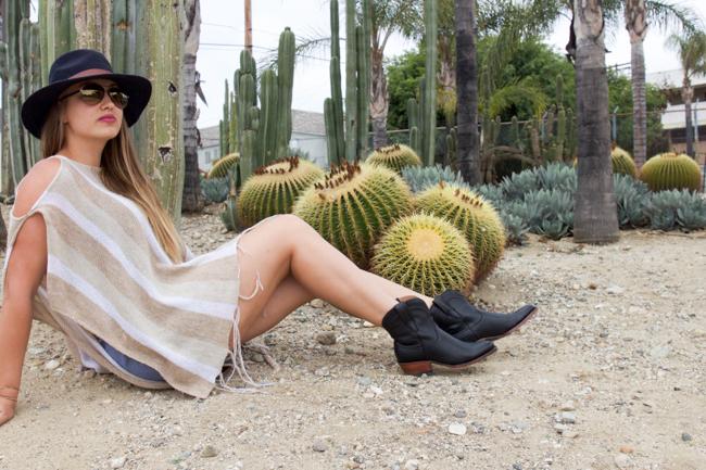 A poncho, denim romper, and Tecovas boots