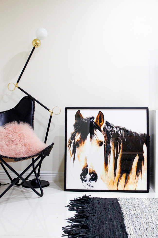oversized equine art with fringe leather rug and modern lamp