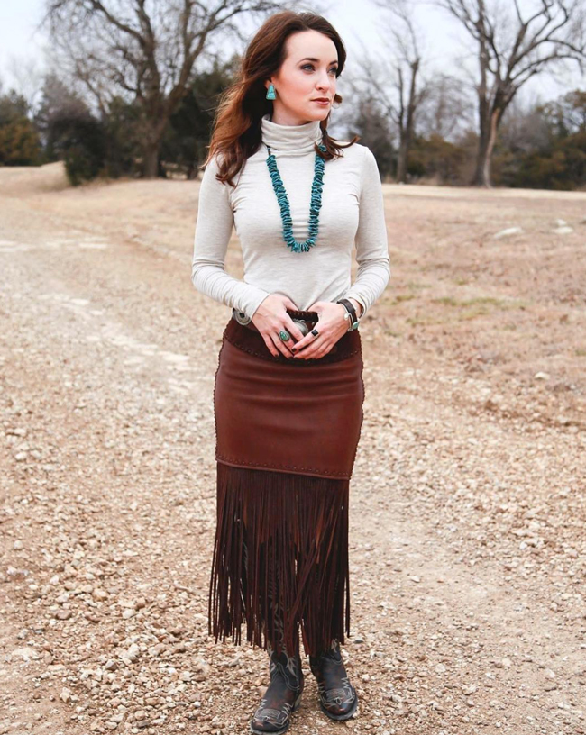 Meg wearing cowboy boots, a fringe skirt, and turquoise