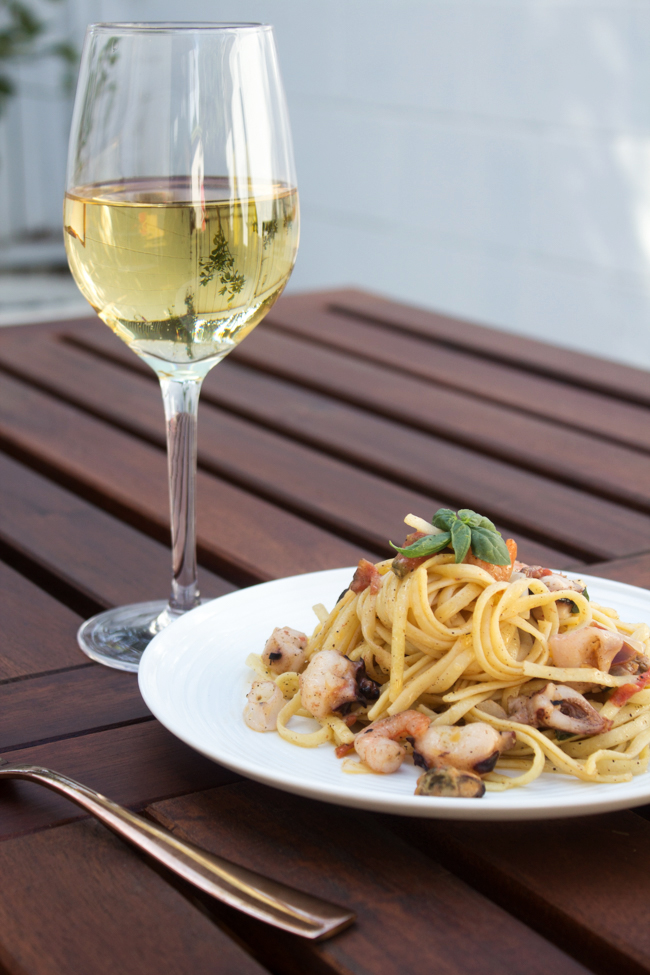 seafood linguine with a glass of wine