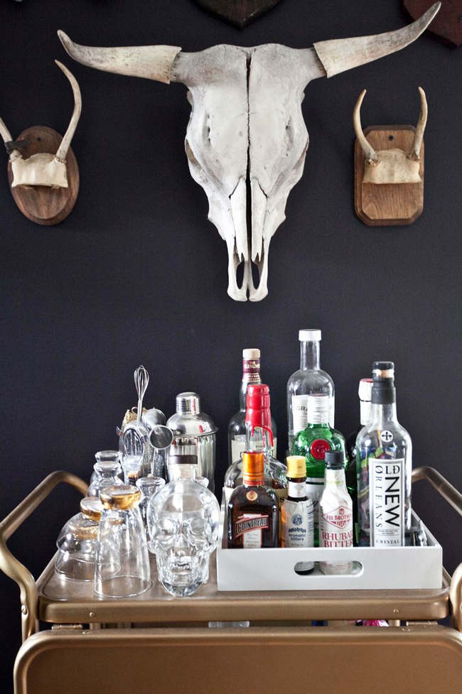 a well stocked bar cart with a steer skull and antlers hanging above it