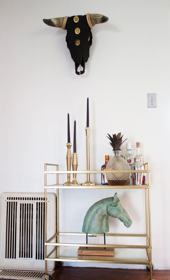 black and gold steer skull hanging above the bar cart