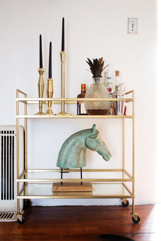 styled West Elm bar cart with a horse head and candle sticks
